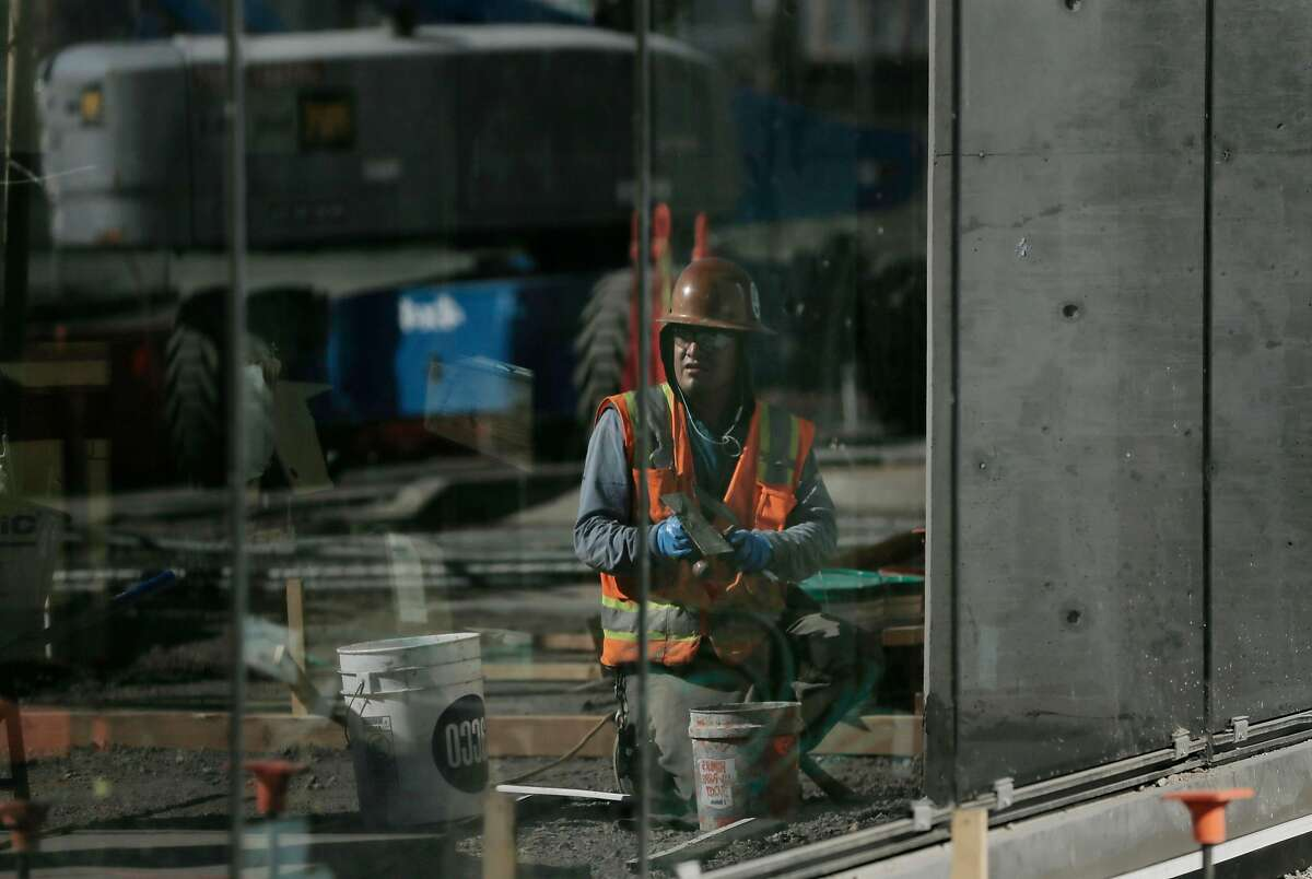 Rolando Hernandez, mason DPR Constuction, is refleceed in at a construction site where Adobe will have an office in the future in San Francisco, Calif., on Friday, February 9, 2018.