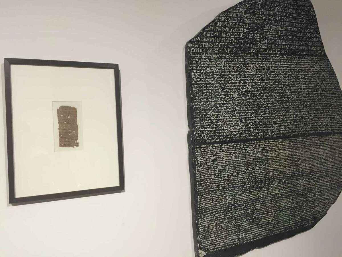 A papyrus fragment with Greek writing from 300-350 B.C.E and a replica of the Rosetta Stone.