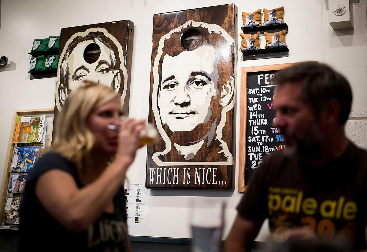 Images of actor Bill Murray, adorning a set of cornhole boards, peer down at Tannery Bend Beerworks patrons in Napa, Calif., on Saturday, Feb. 17, 2018. Seated are Marlow Bruce, left, and Mike Daniel.