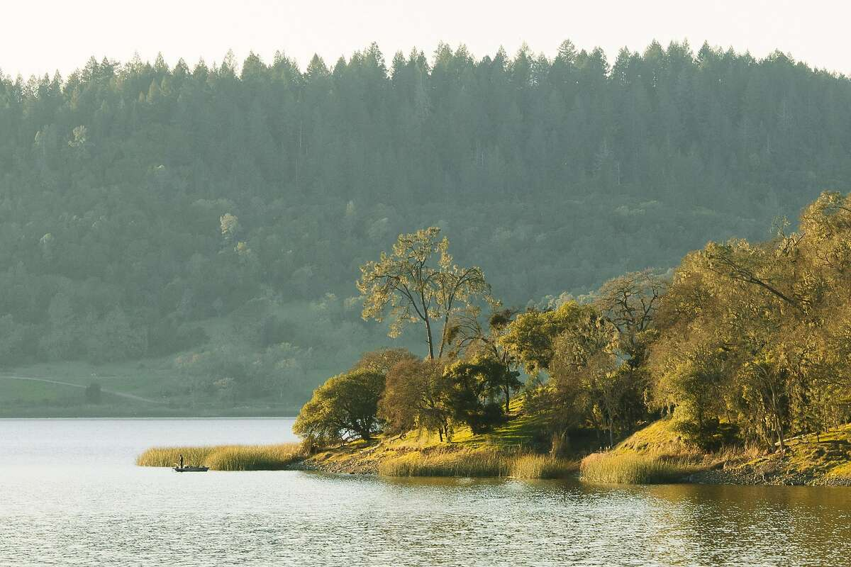 A fisherman in a small boat tries his luck along the banks of the Moore Creek Park on Lake Hennessey near St. Helena.