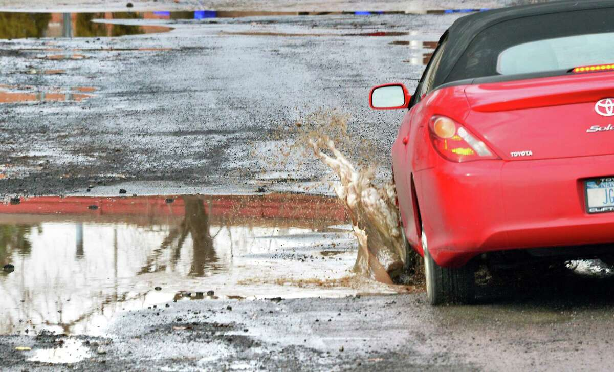 A car splashes through water filled potholes on Hawkins St. between Brevator and Rosemont streets on Tuesday Feb. 20, 2018 in Albany, NY. (John Carl D'Annibale/Times Union)