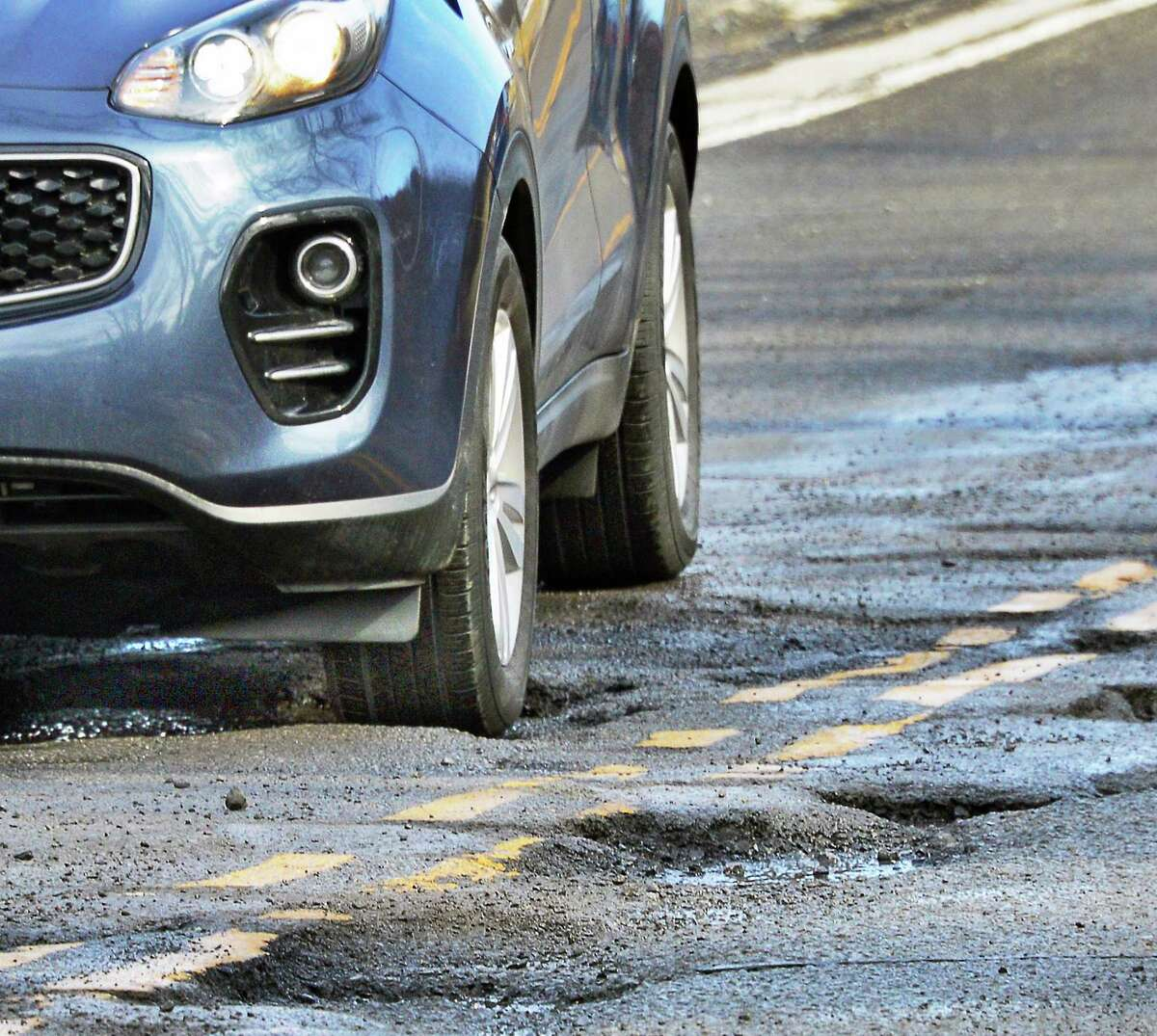 A car navigates through potholes on Hackett Boulevard between Holland Ave. and Crown Terrace Tuesday Feb. 20, 2018 in Albany, NY. (John Carl D'Annibale/Times Union)