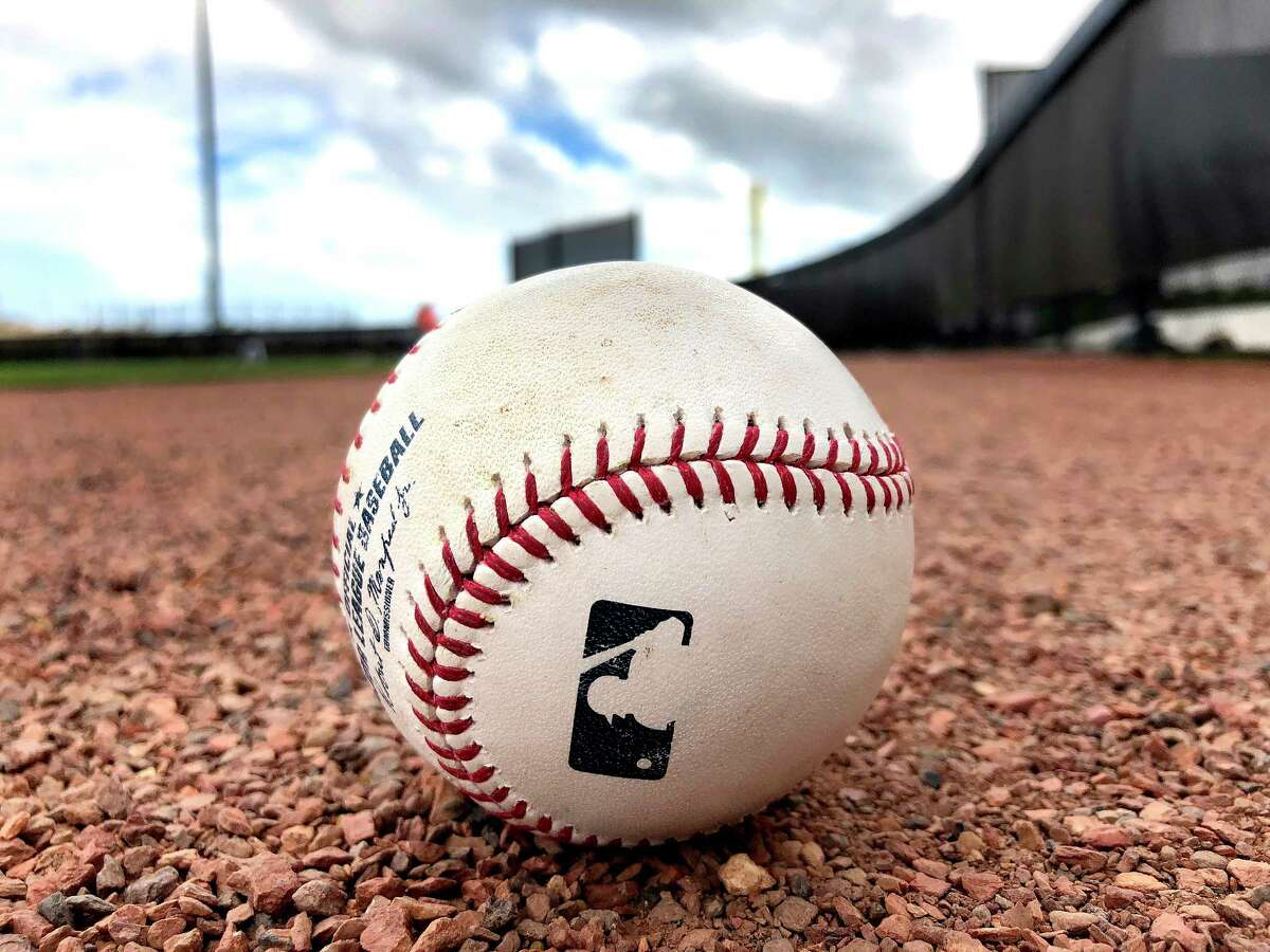 A baseball sits on the warning track of a field during spring training at The Ballpark of the Palm Beaches, Tuesday, Feb. 20, 2018, in West Palm Beach.