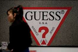 An employee passes the Guess logo inside of one of the company's retail stores in New York on March 12, 2012. (