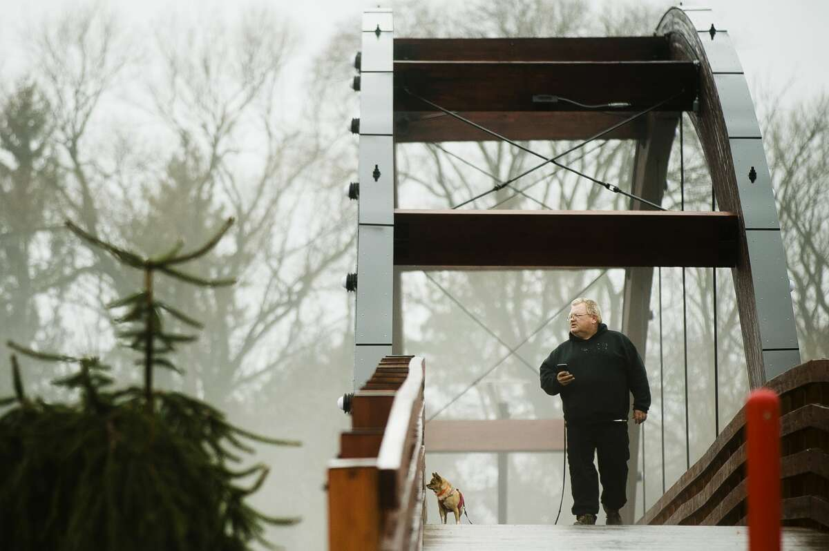 Paul Westley of Midland walks across the Tridge with his dog, Lulu, as fog blankets Chippewassee Park on Tuesday, Feb. 20, 2018. (Katy Kildee/kkildee@mdn.net)