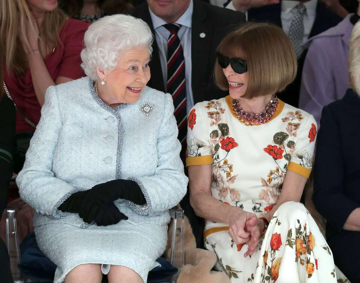 Britain's Queen Elizabeth II, accompanied by British-American journalist and editor, Anna Wintour (R), views British designer Richard Quinn's runway show before presenting him with the inaugural Queen Elizabeth II Award for British Design, during her visit to London Fashion Week's BFC Show Space in central London on February 20, 2018. / AFP PHOTO / POOL / Yui MokYUI MOK/AFP/Getty Images
