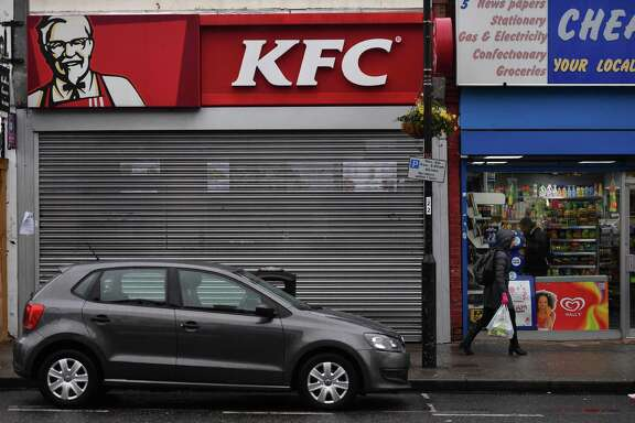 Pedestrians pass outside a closed KFC fast food store in south London on February 19, 2018. US fast food chain KFC said on February 19 it had been forced to close many restaurants in Britain because of a new supplier failing to deliver chicken in time, generating some tongue-in-cheek outrage on Twitter.