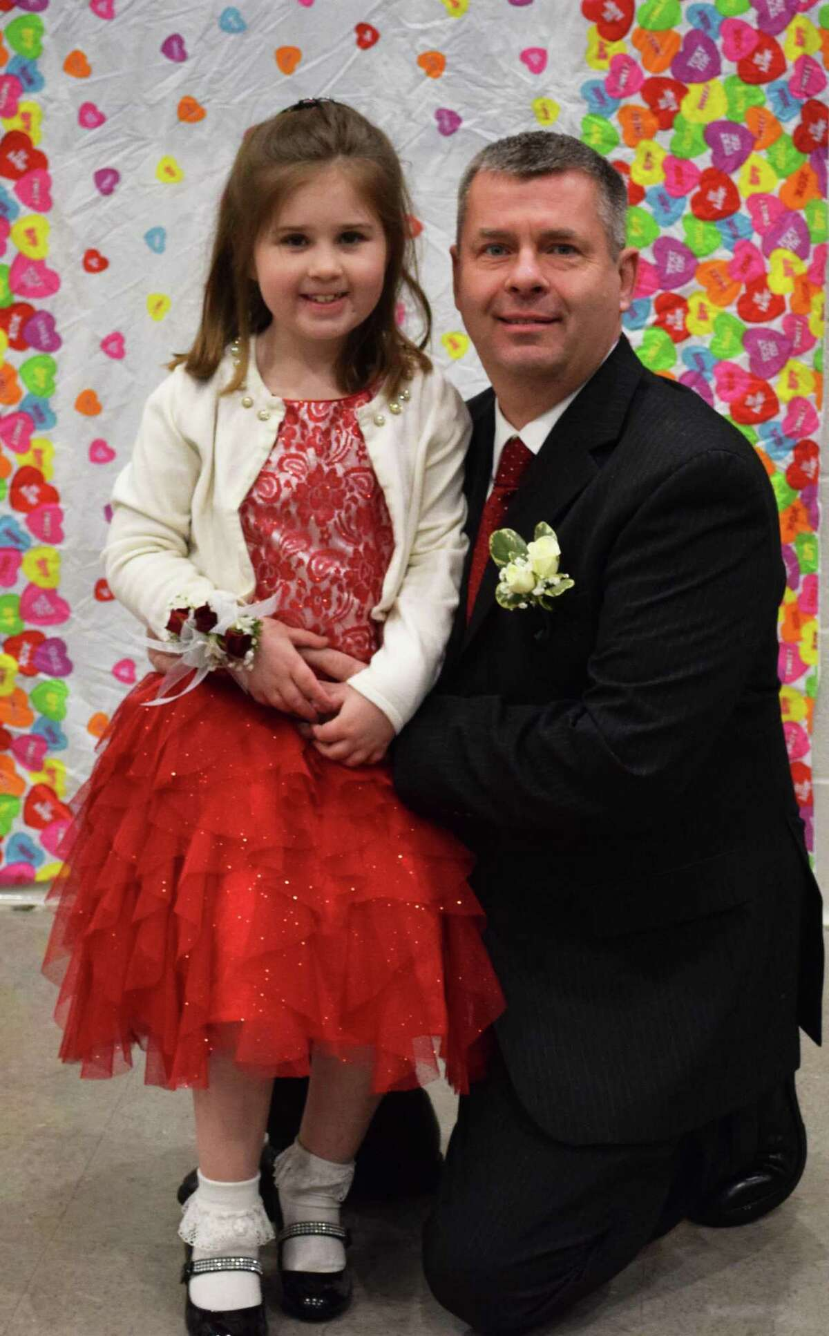 Spectrum/Rob Dempster and his daughter, Eleanor, 7, pause to have their photo taken at the start of the New Milford Girl Scouts annual Sweetheart Dance, sponsored this year by Troop 40236, at New Milford High School Feb. 9, 2018.