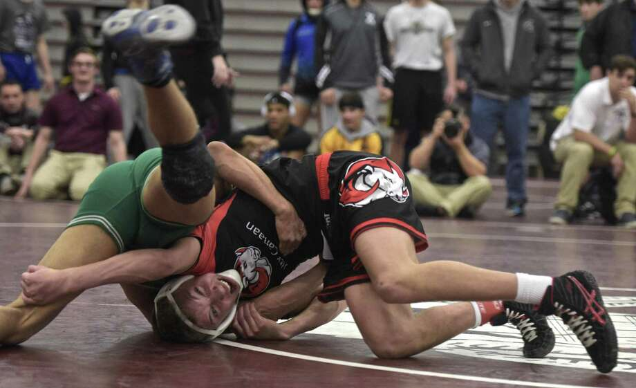 New Milford's Melquisedec Ortiz and New Canaan's Justin Mastroianni grapple in the 126-pound weight class for the championship of the Class L wrestling tournament on Saturday in Bristol. Photo: H John Voorhees III / Hearst Connecticut Media / The News-Times