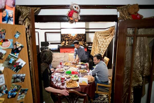 Shaheen Nassimi, 20, standing, serves food as his family eats dinner in their Oakland, Calif., home on Sunday, Feb. 11, 2018. Seated at right is his father Abdul Nassimi.