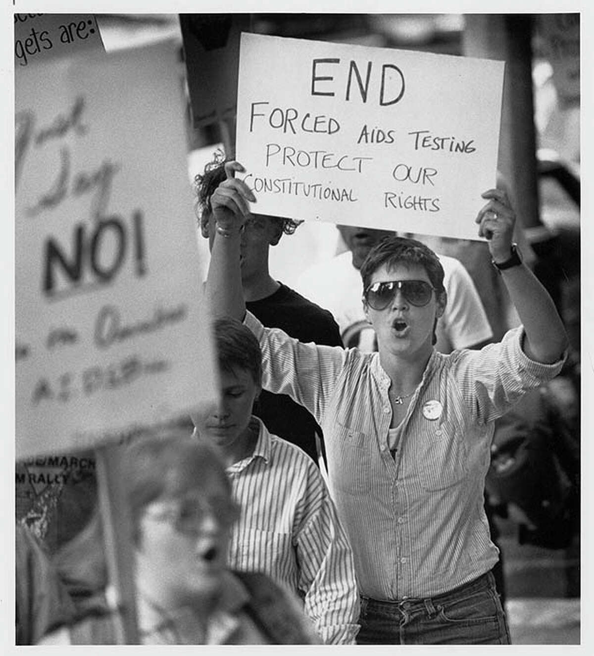 In June 1988, about two dozen people protested forced AIDS testing outside the King County Courthouse. This image shows members of the Stonewall Committee for Lesbian/Gay Rights at that event, picketing in protest of a court order requiring testing of Steven Farmer, a convicted sex offender, against his will.