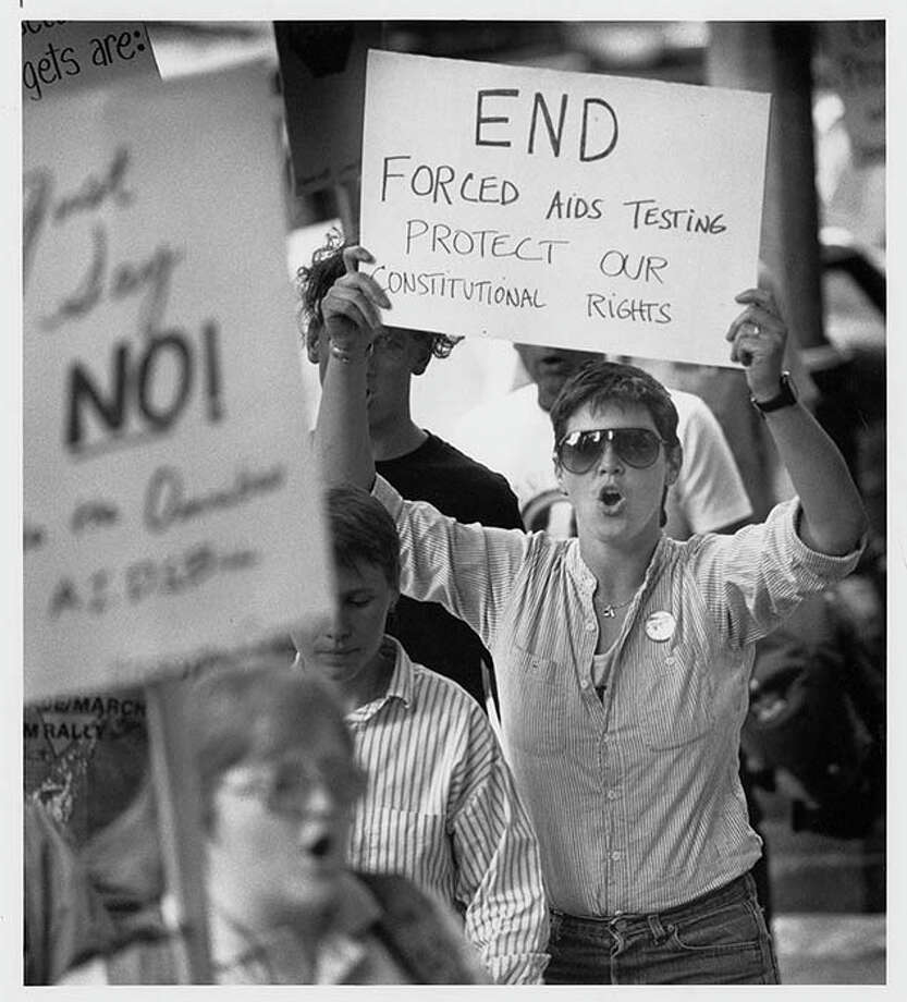 In June 1988, about two dozen people protested forced AIDS testing outside the King County Courthouse. This image shows members of the Stonewall Committee for Lesbian/Gay Rights at that event, picketing in protest of a court order requiring testing of Steven Farmer, a convicted sex offender, against his will. Photo: PI FILE