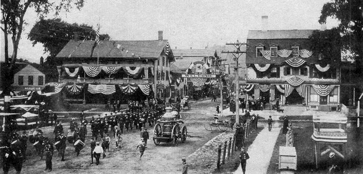 """The firemen's parade was one of the many special events held in New Milford more than 100 years ago. Shown above is the parade in the village center of New Milford, circa 1900, just pre-dating the Great Fire of 1902 that destroyed the New England House, left center, at the corner of Main and Bank streets. To the right is the United States Hotel, which was razed in 1927 on the present site of Robertson Jewelers. If you have a """"Way Back When"""" photo you'd like to share, contact Deborah Rose at drose@newstimes.com or 860-355-7324."""