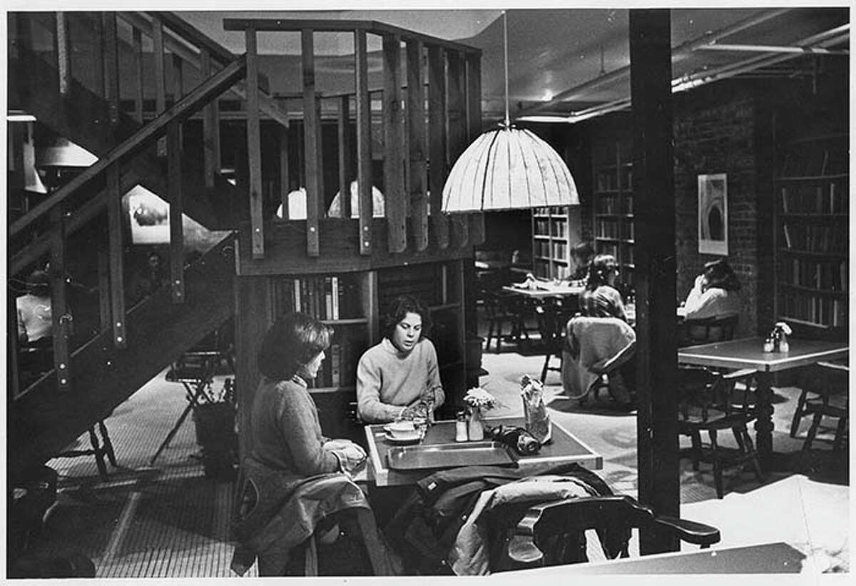 """Title: Basement cafe at Elliott Bay Book Company, Seattle, March 6, 1980 Photographer: Haller, Grant M. Date: 1980 Caption: In spite of various threats over the years--huge chains, online shopping, and electronic reading devices--independent book stores in Seattle have continued the thrive, and the city is home to more per capita than any other U. S. city. The Elliott Bay Book Company was founded in 1973 by Walter Carr in the historic (1890) Globe Building on First Avenue and Main Street in Pioneer Square. It was later sold and then moved in 2010 to Capitol Hill, at 1521 10th Avenue. Long a local favorite, the Associated Press also lists Elliott Bay Book Co. as one of America's nine """"destination"""" bookstores."""