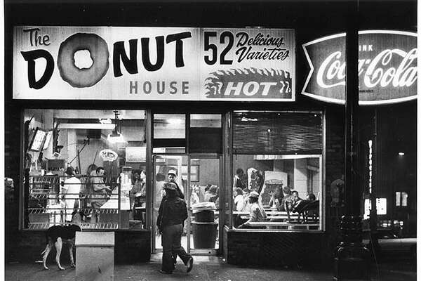 Title: The Donut House, Seattle, October 17, 1981 Photographer: Haller, Grant M. Seattle Post-Intelligencer Date: 1981 Caption: The Donut House, on the southeast corner of First Avenue and Pike Street, was a popular hangout for runaways and street people. In 1979, a youth was stabbed to death in the doorway. Yet, according to the Seattle Post-Intelligencer, the young people who hung out at The Donut House thought of themselves as a family, and the shop as a drop-in center.   In October 1979, an organized crime task force raided the business. Shop operator Guenter Mannhalt was charged with dealing drugs and masterminding robberies at numerous restaurants in the Seattle and Bellingham areas. Several employees had committed the crimes and testified against him, and he was convicted in September 1981. In November 1981, the owners of the building decided not to renew Mannhalt's lease, and The Donut House closed.   Here, the bright lights of the Donut House shine onto First Avenue as customers enjoy nighttime snacks. The dog (left) appears to be hoping for a taste of one of the 52 Delicious Varieties.