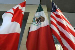 """(FILES) This file photo taken on September 24, 2017 shows the Mexican, US and  Canadian flags in the lobby where the third round of the NAFTA renegotiations took place in Ottawa, Ontario. Canada announced on January 23, 2018 it will sign on the Trans Pacific Partnership, moving to diversify its trade relationships  as Canadian, US and Mexican negotiators kicked off a sixth round of talks on a 1994 free trade pact that Washington has threatened to dump. Canada had initially balked at joining the proposed TPP last year, acting as the main holdout in negotiations after US President Donald Trump decided in early 2017 to go it alone under his """"America First"""" policy.  / AFP PHOTO / Lars HagbergLARS HAGBERG/AFP/Getty Images"""