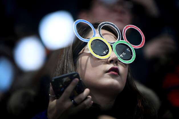 A fan wearing a mask watches the curling men's round robin session between South Korea and Switzerland during the Pyeongchang 2018 Winter Olympic Games at the Gangneung Curling Centre in Gangneung on February 20, 2018. Photo: WANG ZHAO/AFP/Getty Images
