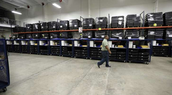 A worker passes voting equipment being staged for the upcoming primary elections at the Bexar County Election offices Feb. 13 in San Antonio. Early voting started Tuesday and ends March 2. The primary election is March 6.