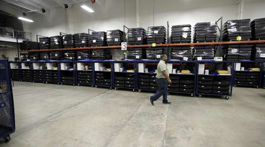 A worker passes voting equipment being staged for the upcoming primary elections at the Bexar County Election offices Feb. 13 in San Antonio. Early voting started Tuesday and ends March 2. The primary election is March 6. Photo: Eric Gay /Associated Press / Copyright 2018 The Associated Press. All rights reserved.