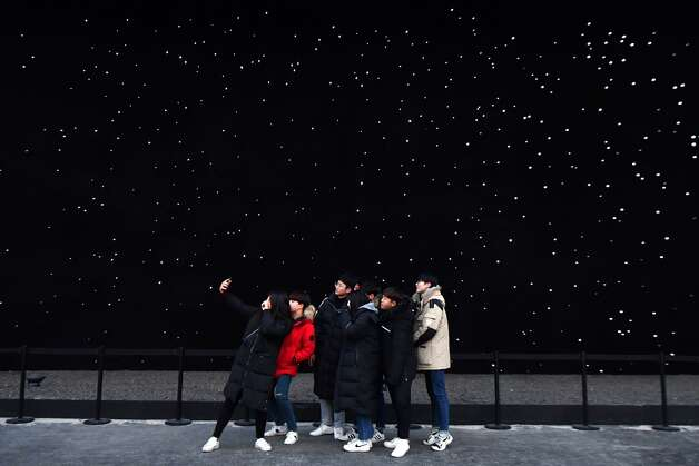 People pose for a selfie at the Olympic Park during the Pyeongchang 2018 Winter Olympic Games in Pyeongchang on February 20, 2018. Photo: FABRICE COFFRINI/AFP/Getty Images