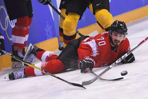 Switzerland's Denis Hollenstein looks at the puck in the men's play-offs qualifications ice hockey match between Switzerland and Germany during the Pyeongchang 2018 Winter Olympic Games at the Kwandong Hockey Centre in Gangneung on February 20, 2018. Photo: JUNG YEON-JE/AFP/Getty Images