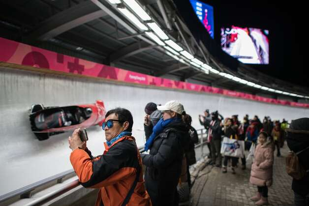 A spectator takes a photo beside the track during the women's bobsleigh heats during the Pyeongchang 2018 Winter Olympic Games at the Olympic Sliding Centre in Pyeongchang on February 20, 2018. Photo: ED JONES/AFP/Getty Images