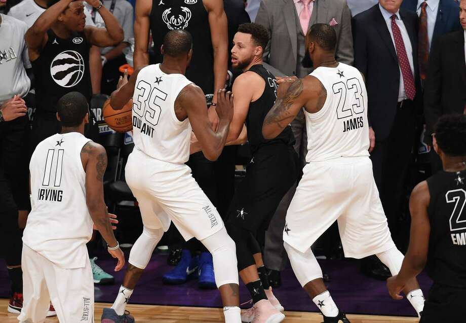Kevin Durant and LeBron James prevent Stephen Curry from getting a shot off in the closing seconds Sunday to preserve a 148-145 victory for Team LeBron in the NBA All-Star game. Photo: Robyn Beck /Getty Images / AFP or licensors
