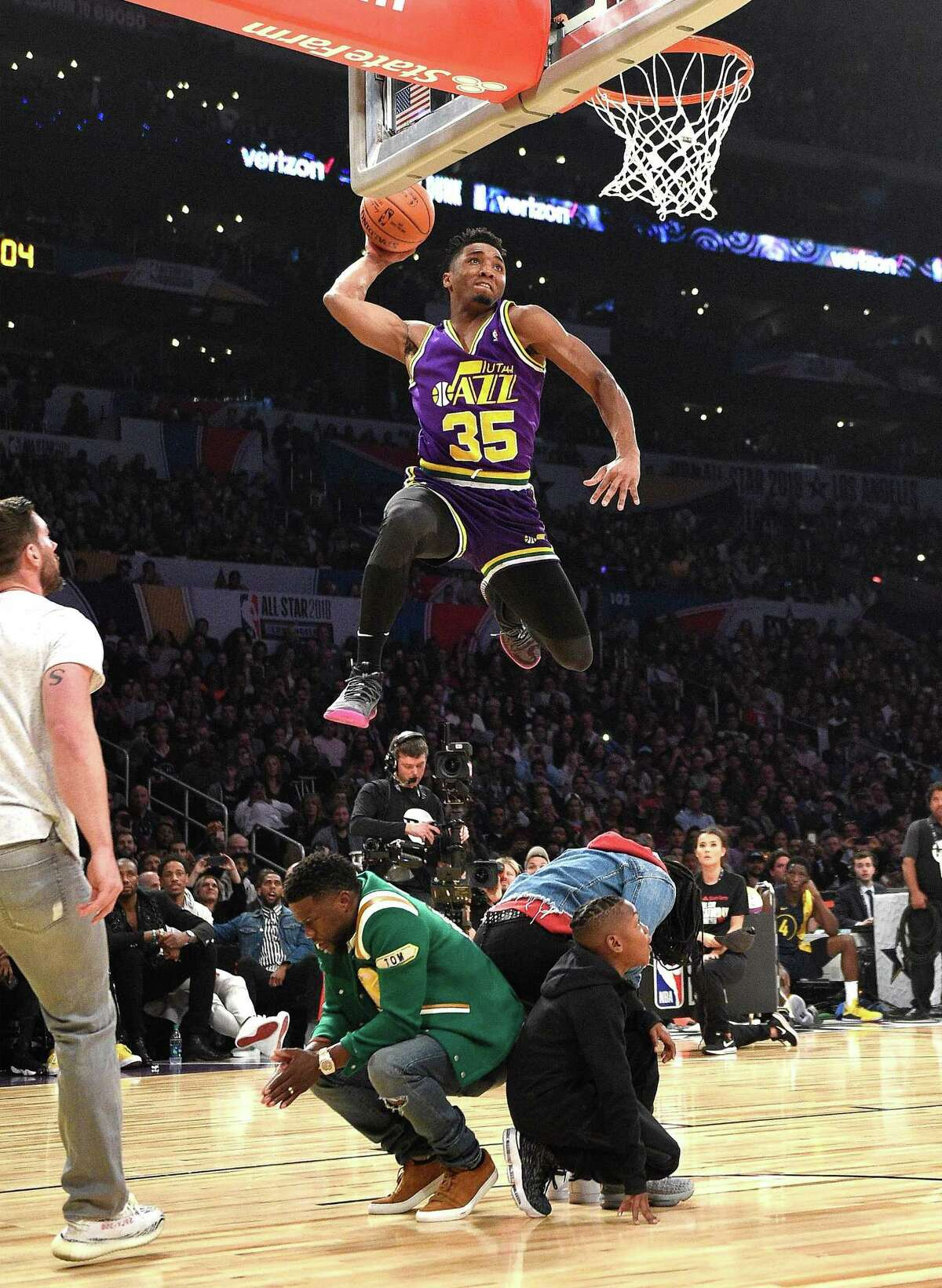 Utah's Donovan Mitchell dunked over Kevin Hart, Jordan Mitchell and Hendrix Hart on his way to winning the 2018 Verizon Slam Dunk Contest at Staples Center Saturday in Los Angeles.