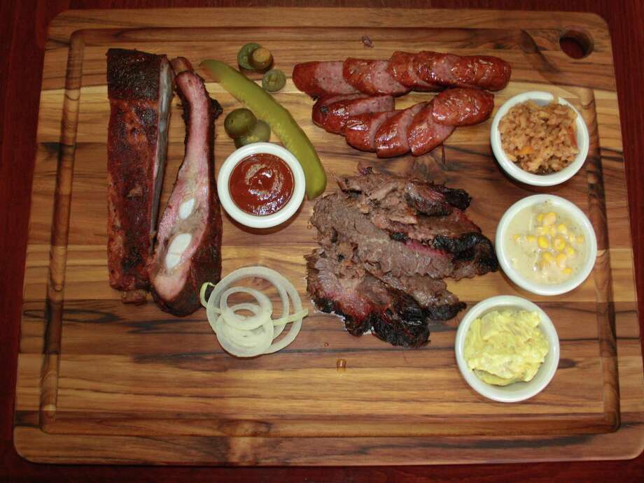 The El Monte BBQ menu keeps it simple with pork spare ribs, sausage and brisket as the only meat options. Sides include Spanish rice, creamed corn, potato salad and (not pictured) baked beans. Photo: Chuck Blount /San Antonio Express-News