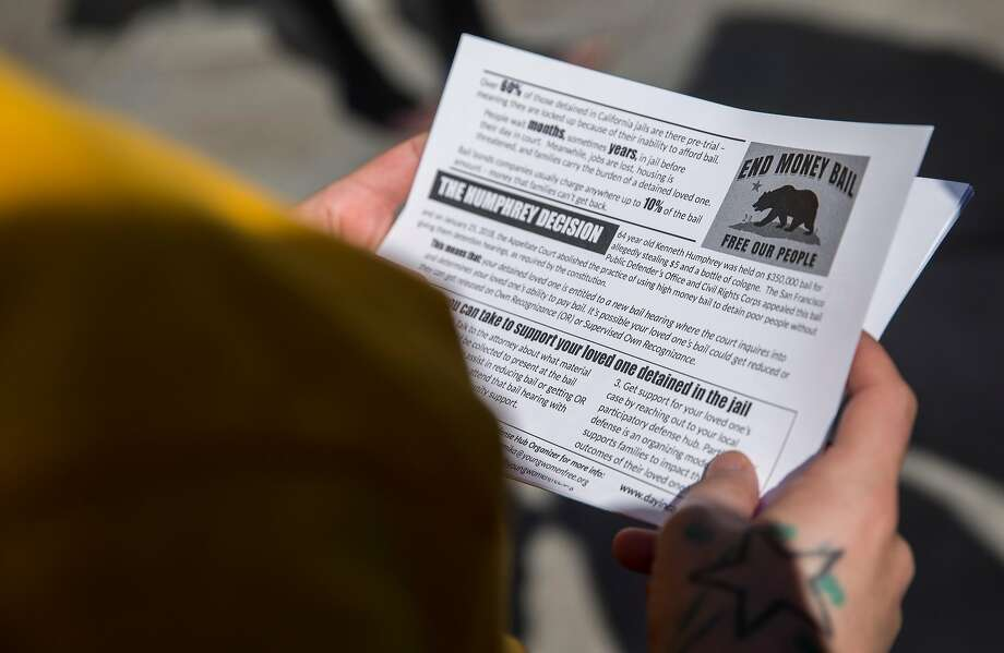 Nancy Ibarra reads over hand-out flyers during a rally calling for the end of the money bail system in California Tuesday, Feb. 20, 2018 at the Hall of Justice in San Francisco. Photo: Jessica Christian, The Chronicle