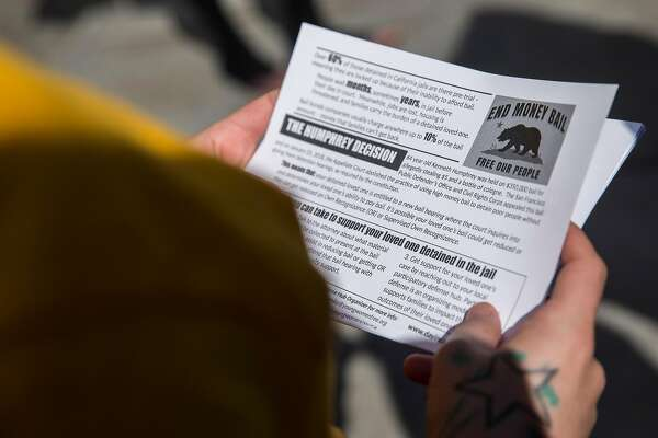 Nancy Ibarra reads over hand-out flyers during a rally calling for the end of the money bail system in California Tuesday, Feb. 20, 2018 at the Hall of Justice in San Francisco, Calif.