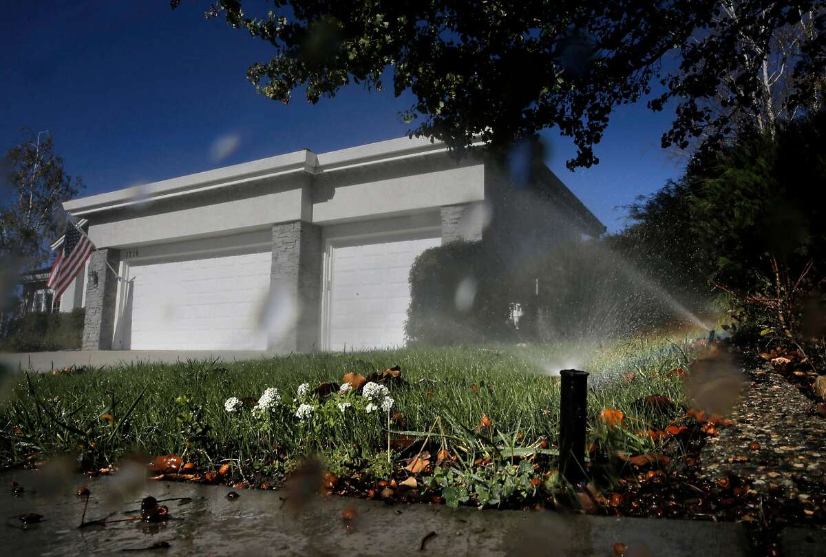 Sprinklers water a lawn at noon in the city of Pleasanton, on November 4, 2015.