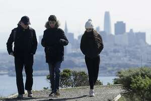 A family dressed for cold weather walks down a path in front of the San Francisco skyline near Sausalito, Calif., Tuesday, Feb. 20, 2018. The very cold air mass from western Canada brought the most frigid temperatures so far this winter and the coldest in years for some locations, the San Francisco/Monterey National Weather Service office said. (AP Photo/Jeff Chiu)