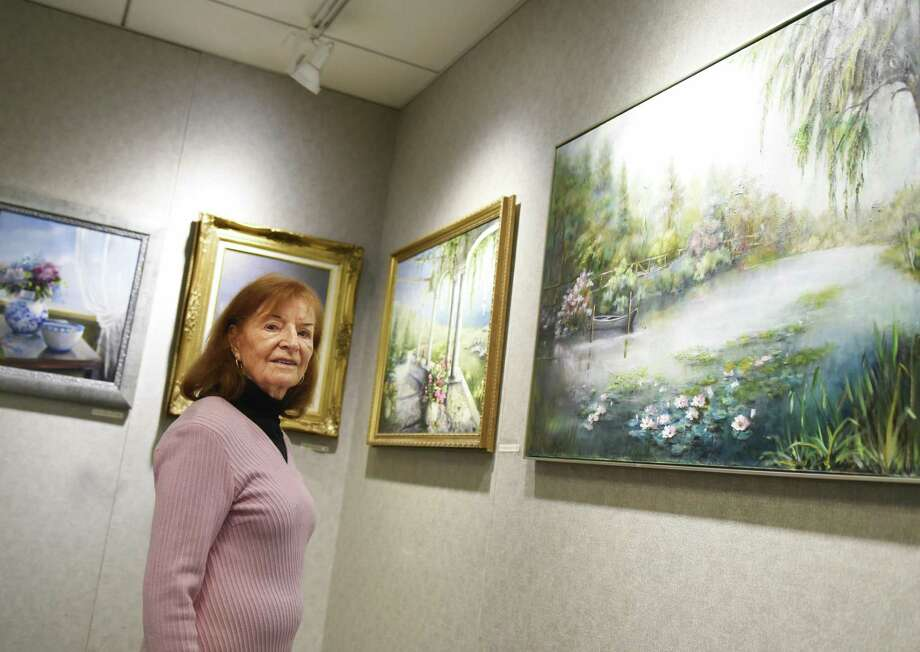 "Greenwich artist Lucie Anderes poses by her work, including the piece ""Luminous Fibration,"" right, on display at the YWCA in Greenwich, Conn. Thursday, Feb. 15, 2018. Anderes's oil paintings feature soft-colored impressionistic scenes and still lifes ranging from her backyard, to Maine, to Morocco. Photo: Tyler Sizemore / Hearst Connecticut Media / Greenwich Time"
