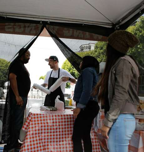 From left: Cas McGee, Christian Ciscle, Adele Sheik and Kayla Tubera set up the Wing Wings fried chicken stand at The Union Street Festival on Saturday, June 6, 2015. Photo: Loren Elliott, The Chronicle