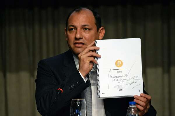 """Venezuelan Minister of Science, Technology and University Education Hugbel Roa holds a document with the financial proposal of the """"Petro"""" cryptocurrency, signed by Venezuelan President Nicolas Maduro, during a press conference at the Central Bank's (BCV) headquarters in Caracas on January 31, 2018. Venezuela created a digital currency called """"Petro"""" to try to combat the economic crisis. / AFP PHOTO / FEDERICO PARRAFEDERICO PARRA/AFP/Getty Images"""