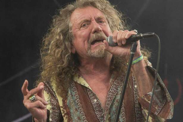 CORRECTS CAPTION TO NOTE THAT GARLAND IS A RESTAURANT IN RALEIGH - FILE - In this June 28, 2014 file photo, Robert Plant performs on the Pyramid main stage at Glastonbury music festival, in England.  Plant and his backing band, Sensational Space Shifters, made their way to Garland restaurant in Raleigh, N.C., after kicking off their U.S. tour on Friday, Feb. 9, 2018, but the eatery was closed. The restaurant's owners showed them a whole lotta love by feeding them free of charge. (Photo by Joel Ryan/Invision/AP, File)