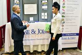 Sanjay Nash, left, from the Bone & Joint Center speaks with job seeker Kahdesha Joseph of Albany during the TU Health Career Job Fair at the Albany Marriott hotel Tuesday Feb. 20, 2018 in Colonie, NY.  (John Carl D'Annibale/Times Union)