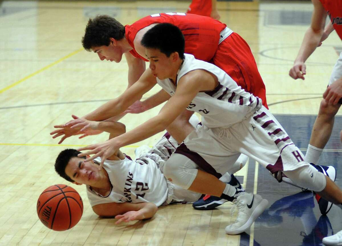 Green Farm Academy's Teddy Brown, at top in back, and Hopkins' Jason Chung, center, and Michael Lau scramble for a loose ball during basketball action in Westport, Conn., on Tuesday Feb. 20, 2018.
