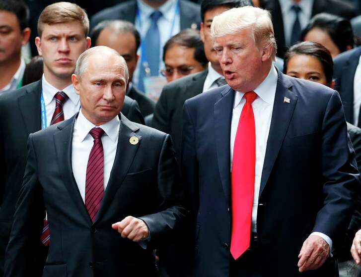 """President Donald Trump, right, and Russia's President Vladimir Putin talk as they make their way to take the """"family photo"""" during the Asia-Pacific Economic Cooperation (APEC) leaders' summit in the central Vietnamese city of Danang on Nov. 11, 2017.  (Jorge Silva / AFP/Getty Images)"""