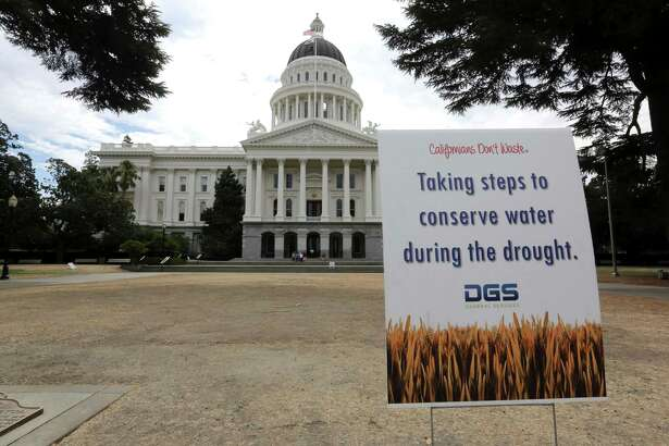 FILE - In this July 8, 2014 file photo, a sign alerts visitors to water conservation efforts is displayed on a parched lawn at the state Capitol in Sacramento, Calif. Members of the state Water Resources Control Board delayed a decision about whether to bring back what had been temporary water bans from California's historic, five-year drought, Tuesday, Feb. 20, 2018.