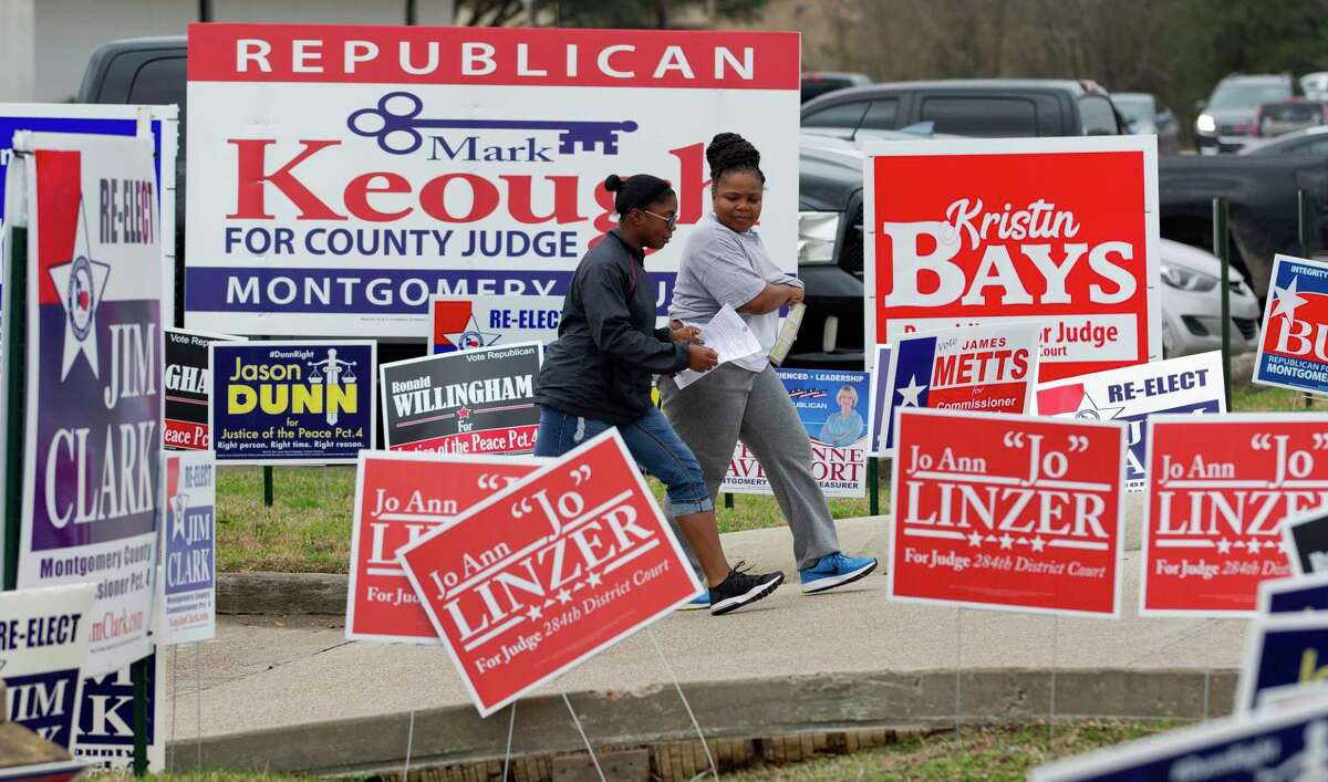Voters walk by political signs that line the street to the East Montgomery County Courthouse on the first day of early voting, Tuesday in New Caney.