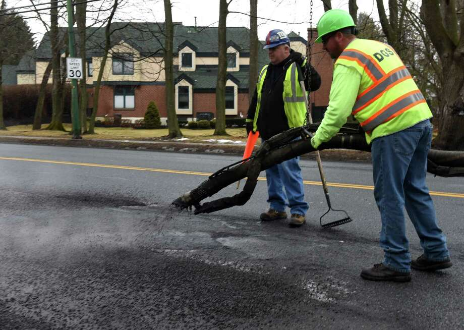 Earl Filkins, left, and Jeff Hunt, right, of the Albany Department of General Services fill potholes along New Scotland Ave. using a Dura Patch process on Friday, Feb. 16, 2018, in Albany, N.Y. The holes are first cleared with compressed air before an emulsion and fill are applied to cover the pothole. (Will Waldron/Times Union) Photo: Will Waldron / 20042954A