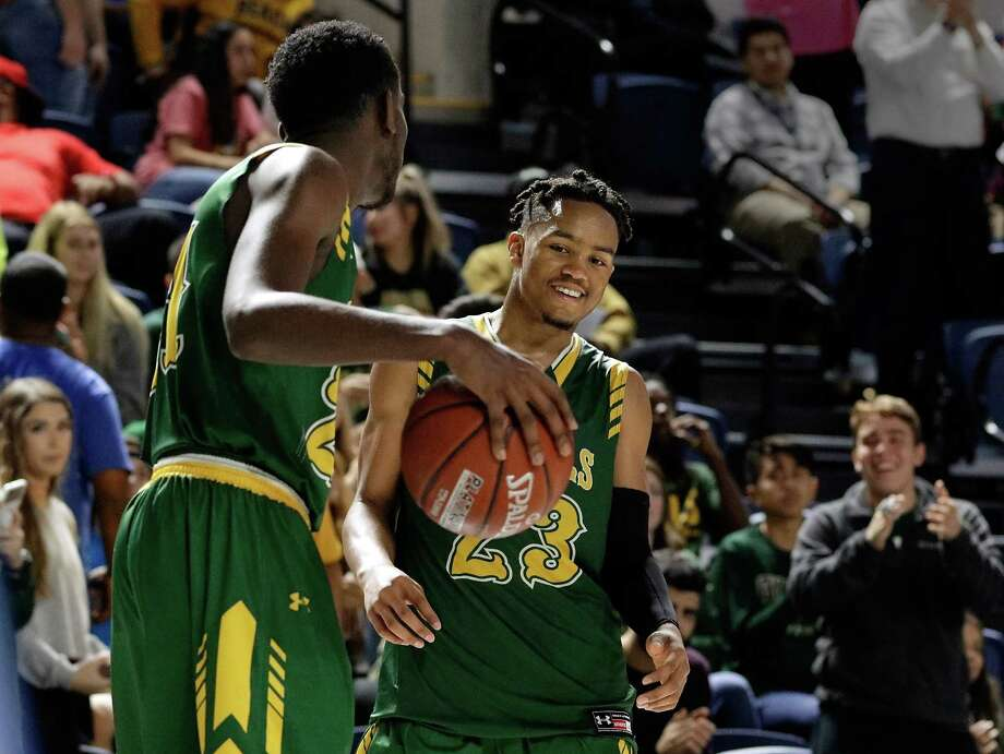 Cy Falls'  Kendall Scott and Nigel Hawkins dribble and grin as they wind down the final seconds on the clock of their win against Bellaire in the Bi-District playoffs at Delmar Field House in Houston, TX, Feb. 20, 2018. (Michael Wyke / For the  Chronicle) Photo: Michael Wyke, For The Chronicle / © 2018 Houston Chronicle