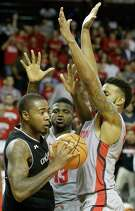 UH's Nura Zanna, center, and Devin Davis, right, crowd Cincinnati's Gary Clark, much like the Cougars are invading the Bearkats' space atop the AAC. UH trails Cincinnati by one game with four regular-season games to play.