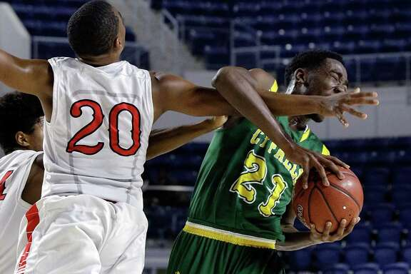 Bellaire's Doug Young reaches in and fouls Cy Falls' Kendall Scott during the first half of their game in the Bi-District playoffs at Delmar Field House in Houston, TX, Feb. 20, 2018. (Michael Wyke / For the  Chronicle)