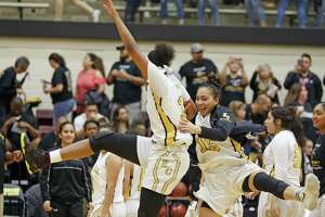 East Centrals' Nalyssa Smith (C) celebrates with East Centrals' Gabriella Ivarra,R at the end of the game from the Class 6A third-round girls high school basketball game between Clark and East Central on Tuesday, February 20, 2018