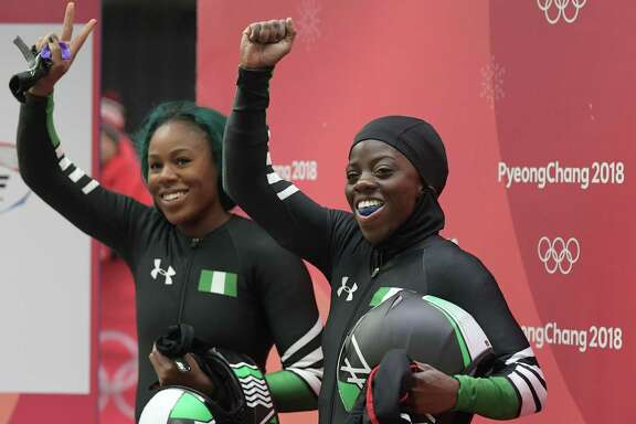 Nigeria's Moriam Seun Adigun (R) and Nigeria's Akuoma Omeoga wave after the women's bobsleigh heat 2 run during the Pyeongchang 2018 Winter Olympic Games, at the Olympic Sliding Centre on February 20, 2018 in Pyeongchang.  / AFP PHOTO / MOHD RASFANMOHD RASFAN/AFP/Getty Images