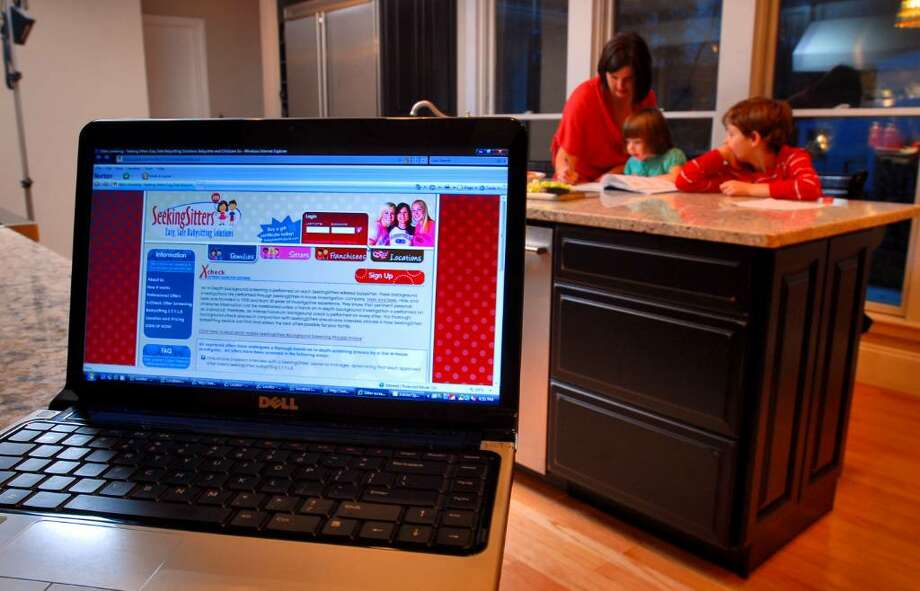 Lori Flynn is the Albany / Saratoga franchise owner of  Seeking Sitters, an online babysitting service, and helps her children Lucia, 3, left, and Hudson, 8, right, with homework in the kitchen of their Delmar, NY home. (Philip Kamrass / Times Union) Photo: PHILIP KAMRASS / 00006258A