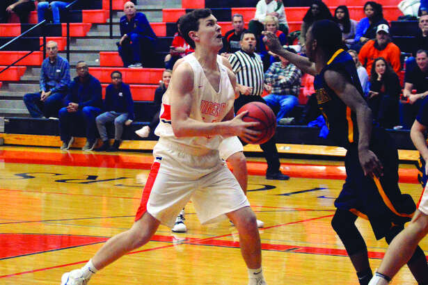Edwardsville senior forward Craig Roberts, left, looks up at the basket in the fourth quarter of Tuesday's game against O'Fallon inside Lucco-Jackson Gymnasium.